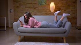 Lanzamiento del primer del caucásico moreno bonito joven femenino usando el teléfono y la mentira sonriente en el sofá en un acog metrajes