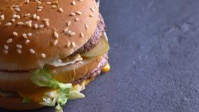 Lanzamiento del primer del cheeseburger souble sabroso con dos empanadas y quesos que hacen girar alrededor en el movimiento almacen de metraje de vídeo