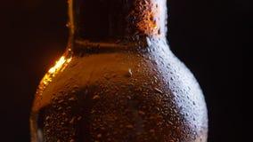 Lanzamiento del primer de brillar el cuello helado de la botella de cerveza con agua que cae abajo con el fondo aislado en negro metrajes