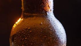 Lanzamiento del primer de brillar el cuello helado de la botella de cerveza con el fondo aislado en negro almacen de video