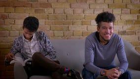 Lanzamiento del primer de dos amigos masculinos jovenes que se sientan en el sofá junto dentro en un apartamento acogedor El homb almacen de metraje de vídeo