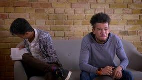 Lanzamiento del primer de dos amigos masculinos jovenes que se sientan en el sof? junto dentro en un apartamento acogedor El homb almacen de video