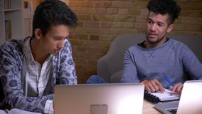 Lanzamiento del primer de estudiantes masculinos indios y afroamericanos usando los ordenadores portátiles y la discusión de sent almacen de video