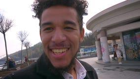 Lanzamiento del primer de fluir afroamericano atractivo joven del turista vivo en el teléfono con el puente en el fondo encendido metrajes