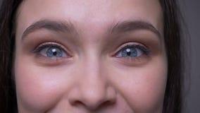 Lanzamiento del primer de la cara femenina atractiva joven con los ojos chispeantes azules que miran la cámara con la expresión f metrajes