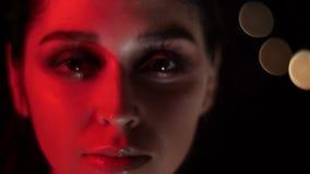 Lanzamiento del primer de la cara femenina bonita con maquillaje imponente con la luz de neón roja y el fondo del bokeh que sonrí almacen de metraje de vídeo