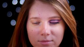 Lanzamiento del primer de la cara femenina caucásica atractiva joven con el medio maquillaje aplicado que mira derecho la cámara almacen de metraje de vídeo
