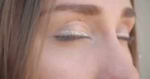 Lanzamiento del primer de la cara femenina caucásica bonita joven con los anillos del pelo y brillar maquillaje con los ojos que  almacen de metraje de vídeo