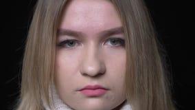 Lanzamiento del primer de la cara femenina caucásica bonita joven que mira la cámara con el fondo aislado en negro almacen de video