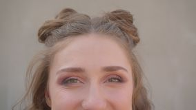 Lanzamiento del primer de la cara femenina caucásica linda joven con los bollos del pelo con los ojos que miran la cámara con la  metrajes