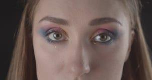 Lanzamiento del primer de la cara femenina de pelo corto caucásica bonita joven con los ojos con el maquillaje del brillo que mir metrajes