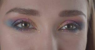 Lanzamiento del primer de la cara femenina de pelo corto caucásica linda joven con el maquillaje del brillo que mira la cámara co almacen de metraje de vídeo