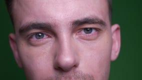 Lanzamiento del primer de la cara masculina atractiva adulta con los ojos que miran la cámara con el fondo aislado en verde almacen de video