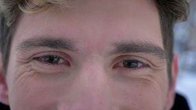 Lanzamiento del primer de la cara masculina caucásica atractiva joven con los ojos marrones que miran la cámara con la expresión  almacen de metraje de vídeo
