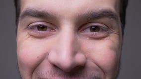 Lanzamiento del primer de la cara masculina joven con los ojos que miran la cámara con la expresión sonriente con el fondo aislad almacen de video