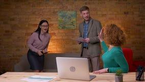Lanzamiento del primer de la empresaria acertada adulta que usa el ordenador portátil que es excitado y que celebra con la hembra almacen de video