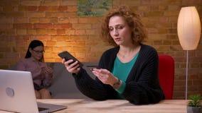 Lanzamiento del primer de la empresaria adulta que hace compras en línea en el teléfono dentro en la oficina El usar femenino del almacen de metraje de vídeo