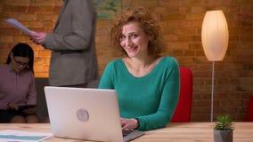 Lanzamiento del primer de la empresaria adulta que mecanografía en el ordenador portátil que mira la cámara y que sonríe dentro e metrajes