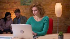 Lanzamiento del primer de la empresaria adulta que mecanograf?a en el ordenador port?til dentro en la oficina Discusión femenina  metrajes