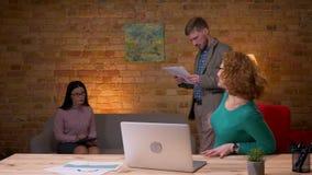 Lanzamiento del primer de la empresaria adulta que usa el ordenador portátil que es excitado y que celebra con dos colegas femeni almacen de video