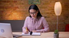 Lanzamiento del primer de la empresaria asiática acertada adulta que mecanografía en el ordenador portátil que toma las notas que metrajes