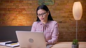 Lanzamiento del primer de la empresaria asiática adulta que mecanografía en el ordenador portátil dentro en la oficina almacen de video
