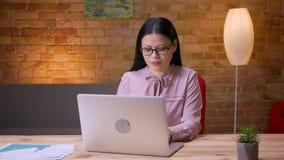Lanzamiento del primer de la empresaria asiática adulta que mecanografía en el ordenador portátil que es feliz y que celebra dent almacen de metraje de vídeo