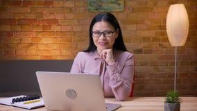 Lanzamiento del primer de la empresaria asiática adulta que mecanografía en el ordenador portátil que mira la cámara y que sonríe almacen de video