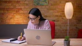 Lanzamiento del primer de la empresaria asiática adulta que mecanografía en el ordenador portátil y que toma notas dentro en la o almacen de video