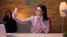 Lanzamiento del primer de la empresaria asiática adulta que toma selfies en el teléfono dentro en la oficina El usar femenino del metrajes