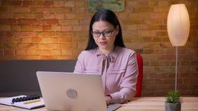Lanzamiento del primer de la empresaria asiática adulta que trabaja en el ordenador portátil que mira la cámara y que sonríe dent almacen de metraje de vídeo
