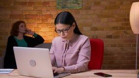 Lanzamiento del primer de la empresaria asiática adulta que trabaja en el ordenador portátil que recibe una notificación en el te almacen de metraje de vídeo