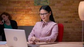 Lanzamiento del primer de la empresaria asiática adulta que trabaja en el ordenador portátil que tiene una llamada de teléfono y  almacen de metraje de vídeo