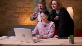 Lanzamiento del primer de la empresaria asiática adulta que usa el ordenador portátil dentro en la oficina Tres empleados que tie metrajes