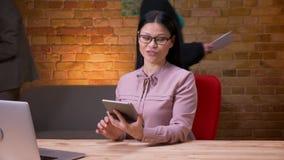 Lanzamiento del primer de la empresaria asiática adulta que usa la tableta delante del ordenador portátil y mostrando la pantalla metrajes