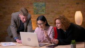 Lanzamiento del primer de la empresaria asiática joven que trabaja en el ordenador portátil que celebra éxito con dos colegas hem almacen de video