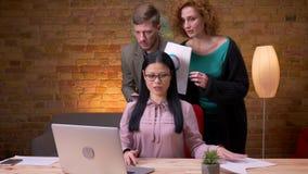 Lanzamiento del primer de la empresaria asi?tica adulta que trabaja en el ordenador port?til dentro en la oficina Tres colegas qu almacen de video
