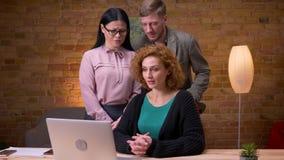 Lanzamiento del primer de la empresaria caucásica adulta que usa el ordenador portátil dentro en la oficina Tres empleados que ti metrajes