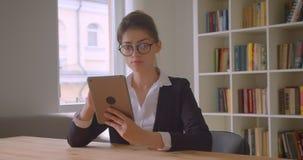 Lanzamiento del primer de la empresaria caucásica bonita joven en vidrios usando la tableta que mira la cámara que sonríe alegre almacen de metraje de vídeo