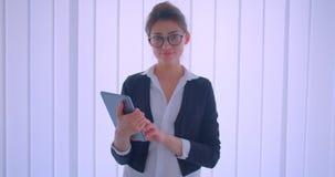 Lanzamiento del primer de la empresaria caucásica bonita joven que sostiene una tableta y que mira la cámara dentro en un cuarto  almacen de video