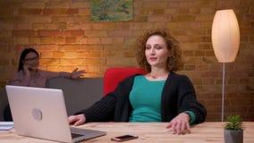 Lanzamiento del primer de la empresaria joven que trabaja en el ordenador portátil que tiene una llamada de teléfono y una relaja almacen de video