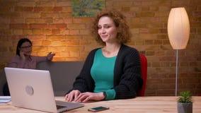 Lanzamiento del primer de la empresaria joven que trabaja en el ordenador portátil que tiene una llamada de teléfono y una relaja metrajes
