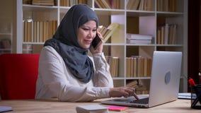 Lanzamiento del primer de la empresaria musulmán adulta en hijab que habla alegre en el teléfono que mecanografía en el ordenador metrajes