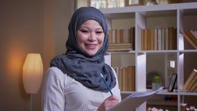 Lanzamiento del primer de la empresaria musulmán adulta que estudia el gráfico en la biblioteca que está pensativa y que mira la  almacen de metraje de vídeo