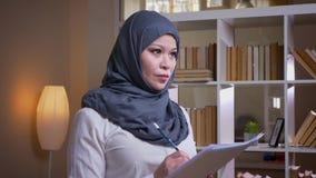 Lanzamiento del primer de la empresaria musulmán adulta que estudia el gráfico en la biblioteca y que busca una solución para el  almacen de metraje de vídeo