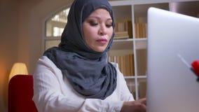 Lanzamiento del primer de la empresaria musulmán adulta que mecanografía en el ordenador portátil que es ocupado y concentrado en almacen de video