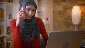 Lanzamiento del primer de la empresaria musulmán atractiva joven que tiene una llamada de teléfono mientras que mecanografía en e almacen de metraje de vídeo