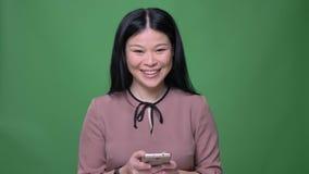 Lanzamiento del primer de la hembra asiática atractiva joven con el pelo negro que manda un SMS en el teléfono y que sonríe con e metrajes