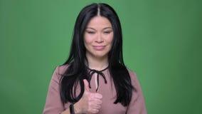 Lanzamiento del primer de la hembra asiática atractiva joven con el pelo negro que muestra un pulgar para arriba y la sonrisa almacen de metraje de vídeo