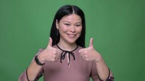 Lanzamiento del primer de la hembra asiática atractiva joven con el pelo negro que sonríe y que gesticula el pulgar encima de dec almacen de metraje de vídeo